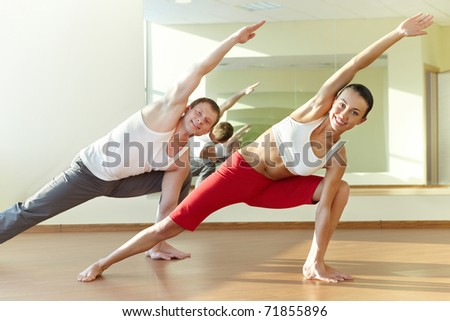 Image of young sporty girl and guy doing physical exercise - stock photo