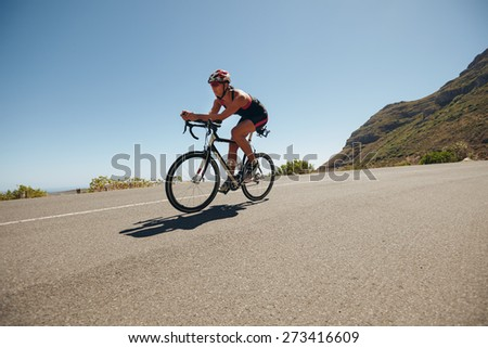 Image of young woman cycling on the country road. Fit female athlete riding down hill on bicycle. Woman doing cycling training. - stock photo