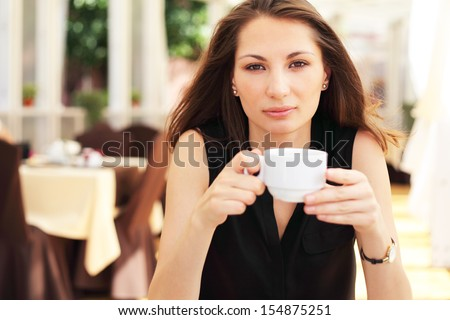 Image of young woman drinks coffee in cafe - stock photo