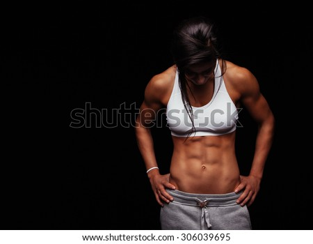 Image of young woman in sports clothing looking down against black background with copyspace. Muscular build female after workout. - stock photo