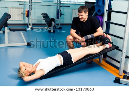 Image of young woman ready for exercising with her personal trainer near by