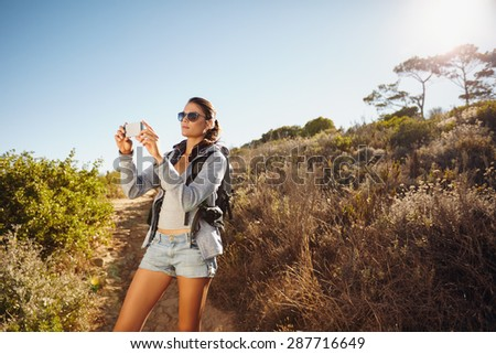 Image of young woman talking photographs with her mobile phone while hiking. Caucasian female trekking on a summer day. - stock photo
