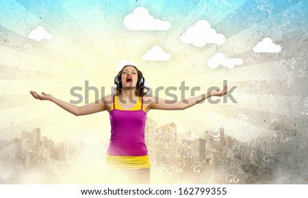 Image of young woman wearing headphones and singing - stock photo
