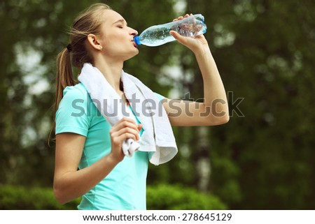 Image of young woman with white towel on her neck drinking water - stock photo