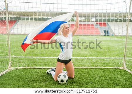 Image or photo of young adult sporty girl hold in hands Russian flag and white and black ball lie on green grass near sexy legs. Goalkeeper woman or football fan stand  on knees against stadium seat - stock photo