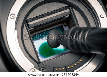 Image photo sensor being cleaned with a lens pen. DSLR APS-C. - stock photo