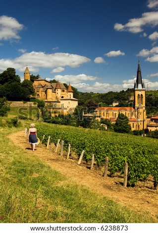 Image shows a blond country girl walking on a gravel road in a village in the French wine-making region of Beaujolais - stock photo