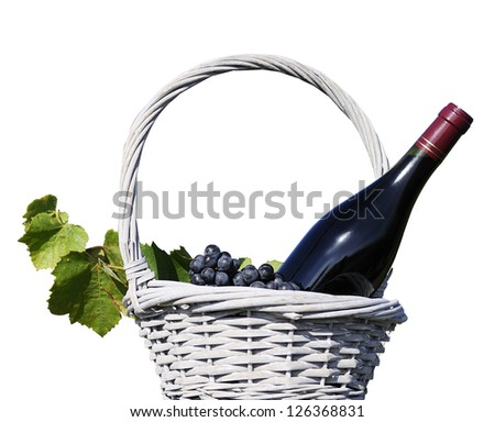 image shows a bottle of red wine in a traditional basket with grapes - stock photo