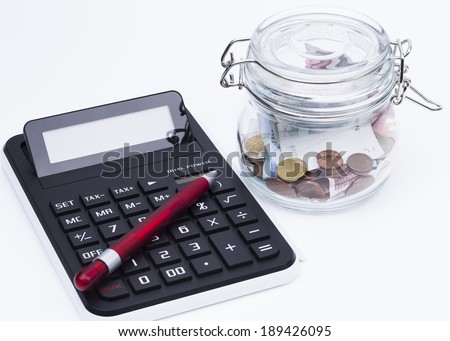 Image shows a calculator and a preserving bottle with money - stock photo
