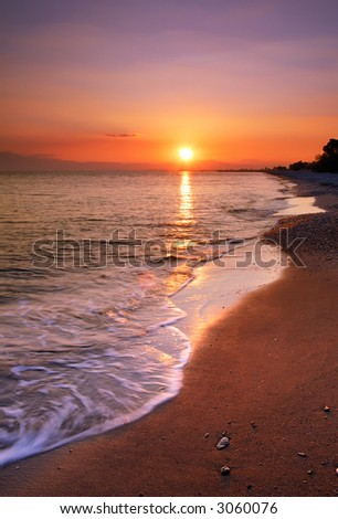 Image shows a deserted beach at sunset - stock photo