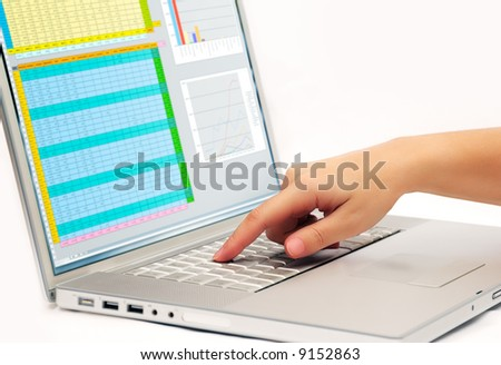 Image shows a finger pressing a key on a contemporary laptop  displaying a business spreadsheet - stock photo