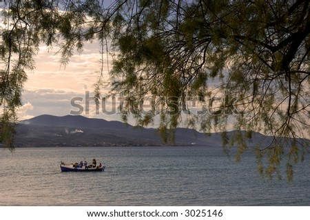 Image shows a fishing boat framed by a tree in the foreground - stock photo