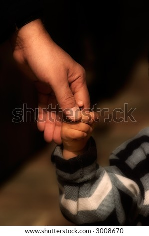 Image shows a hand of an adult holding the hand of a small child - stock photo