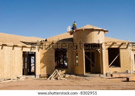 Image shows a home under construction at the roofing phase.  Ideal for roofing advertising and other home construction promotional inferences. - stock photo