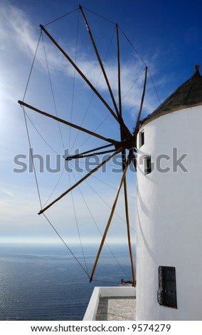 Image shows a large windmill, on the Greek island of Santorini, overlooking the Aegean Sea