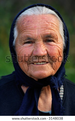 Image shows a portrait of an old Greek happy lady, wearing a scarf - stock photo