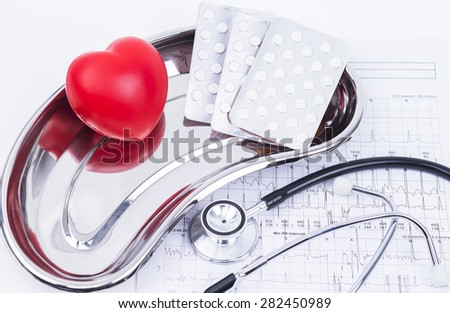 Image shows a red rubber heart with stethoscope and pills on a cardiogram - stock photo