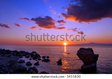 Image shows a sunset over the Messinian bay, Greece, with a rocky seascape in the foreground - stock photo
