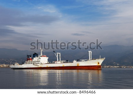 Image shows a white commercial ship photographed from the side