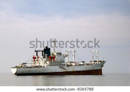 Image shows a white merchant ship floating over calm waters - stock photo