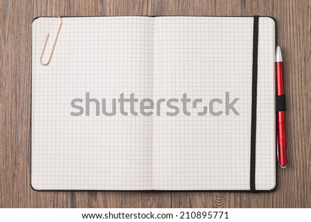Image shows an empty notebook opened on wood-ground - stock photo