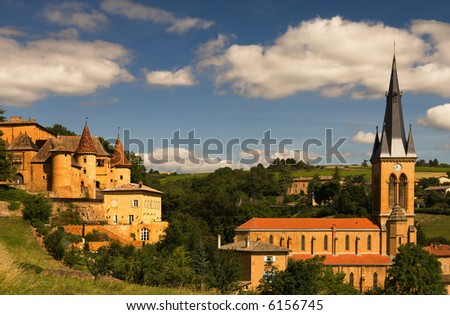 Image shows an old chateau and a church in a village in the famous wine making region of Beaujolais, France
