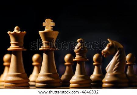 Image shows chess pieces around the white King, photographed from a low angle and with selective focusing on the king. - stock photo