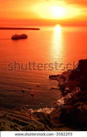 Image shows one of the famous sunsets in Santorini, greece, while a cruise ship is traveling towards the open sea - stock photo