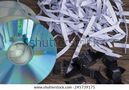 Image shows paper shavings, mag tape shred and compact disks - stock photo