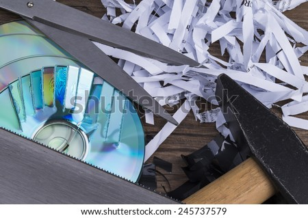Image shows paper shavings, magtape shredd, compact disks and some tools - stock photo