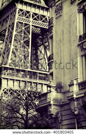 Image taken at Champs du Mars in Paris France with a section of the Eiffel Tower visible behind the corner of the street. Image in sepia. - stock photo