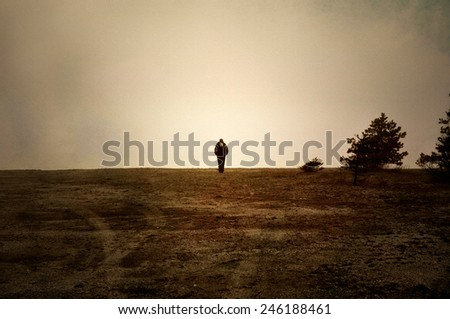 Image textured with soft sandstone of human walking alone on moor. - stock photo