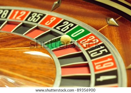 image with a casino roulette wheel with the ball on number 0 - stock photo