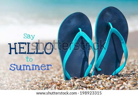 Image with text say hello to summer with pair of blue flip flops on sand beach - stock photo