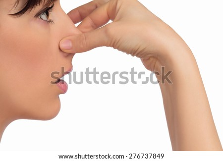 Image with woman's face holding her nose with hand - stock photo