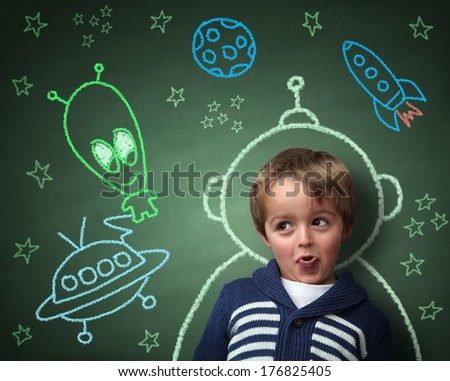Imagination and dreams of a child, dressed as a space man in front of a blackboard with chalk drawings of space rocket and alien, concept for aspirations and daydreaming - stock photo