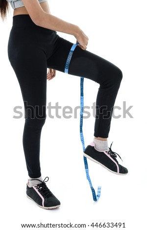 ime for diet slimming weight loss. Fitness woman fit girl in sportswear with measure tape measuring her thigh on white - stock photo