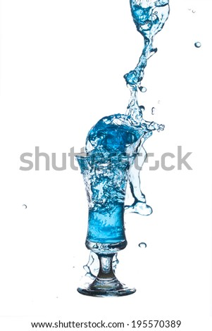 IMG_8341.JPG blue cocktail splashing from glass on white background.  - stock photo
