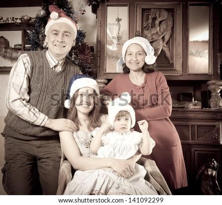 Imitation of antique photo of happy family in Santa hat celebrating Christmas - stock photo