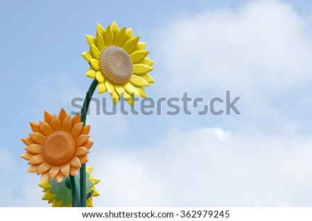 Imitation of sunflower at the park with cloud and blue sky.