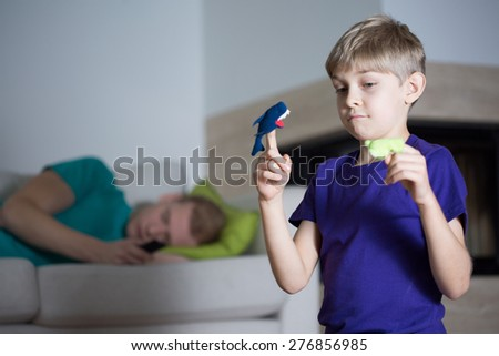Immature dad is sleeping during his son playing alone - stock photo