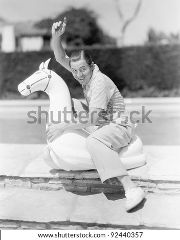 Immature looking man riding a rubber water toy - stock photo
