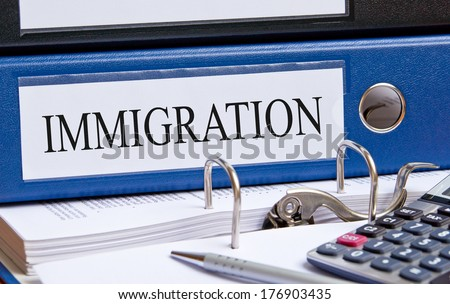 Immigration - blue binder on desk with calculator and pen - stock photo