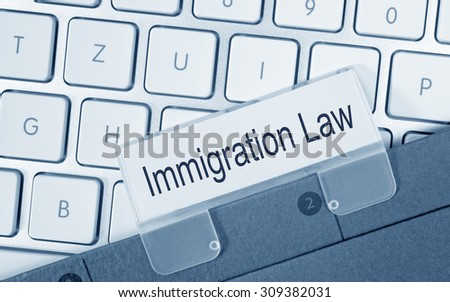 Immigration Law - folder on computer keyboard in the office - stock photo