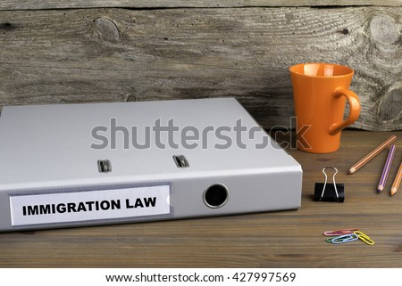 Immigration Law - folder on wooden office desk - stock photo