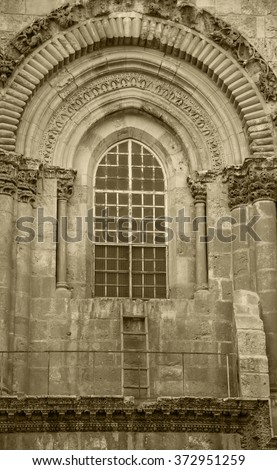 Immovable Ladder (Status Quo Ladder) under the window of Church of the Holy Sepulchre in Jerusalem (Israel). Immovable Ladder is symbol of divisions and religious disputes within Christian World.  - stock photo
