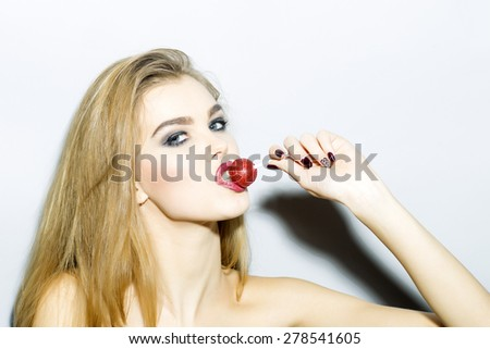Impassioned blonde girl portrait with bright make up looking forward holding and licking round red sugar candy standing on light gray background copyspace, horizontal picture - stock photo