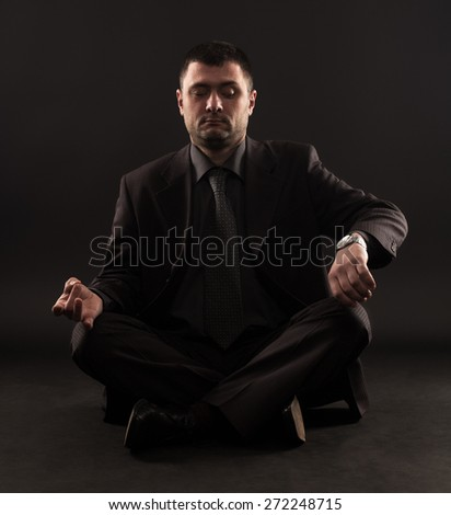 Impatient businessman can not meditate because he looking at the time.