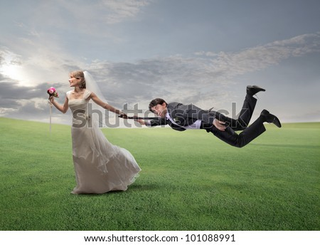Impatient happy wife pulling her husband by his arm and running on a green meadow - stock photo
