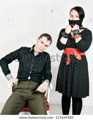 Imperious man and woman with tied mouth in handcuffs - stock photo